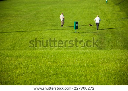 Zagreb, Croatia - October 18, 2014: Two people walking their dog in the park. - stock photo