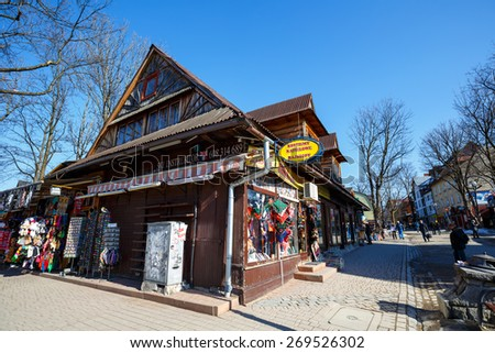ZAKOPANE, POLAND - MARCH 10, 2015: Formerly residential building, nowadays commercial building, built of wood approx in 1900, located at Krupowki, the main pedestrian street in the city  - stock photo