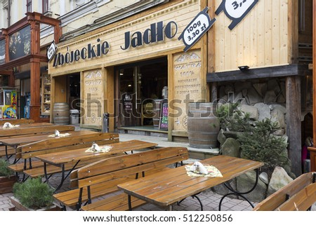 ZAKOPANE, POLAND - SEPTEMBER 20, 2016: Tables and benches belonging to outdoor restaurant named Zbojnickie Jadlo waits for guests. It is at street Krupowki street in the downtown.