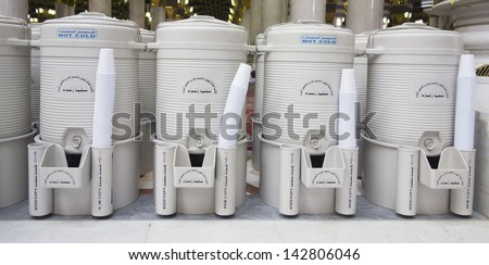 Zamzam water in plastic drums are provided freely for pilgrims in Madinah Mosque, Saudi Arabia. - stock photo