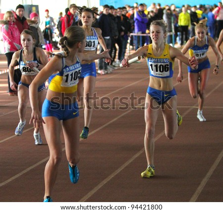 ZAPORIZHIA,UKRAINE - JAN 31: (L-R) Mudrova Aleksandra, Mironova Anastasia, Fesuk Marina run the relay race on Ukainian Junior Track and Field Championships on January 31, 2012 in Zaporizhia, Ukraine - stock photo