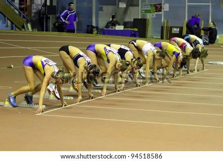 ZAPORIZHIA, UKRAINE - JAN 30: Unidentified girls, age group - 17, on the start of the 60 meters dash during the Ukainian Junior Track and Field Championships on January 30, 2012 in Zaporizhia, Ukraine - stock photo