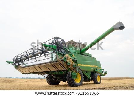 ZAPORIZHZHYA, UKRAINE - July 28, 2015: John Deere Combine Harvester in the Wheat Field. - stock photo