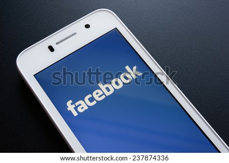 ZAPORIZHZHYA, UKRAINE - NOVEMBER 07, 2014: White Smart Phone with Facebook Social Network Log In Screen on the Black Table. - stock photo