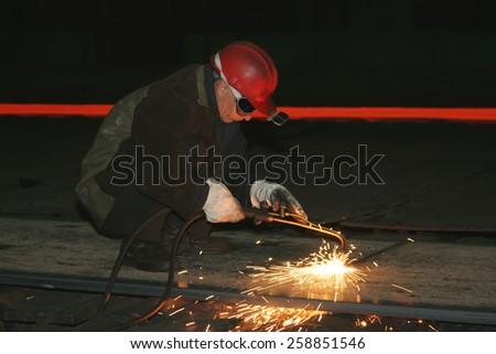 Zaporozhye, UKRAINE - 26 November 2008: Metallurgical factory. Worker welding the steel part - stock photo