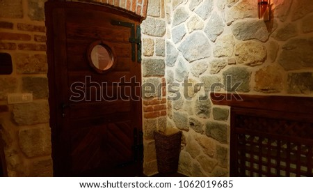Zaton Mali, Croatia - 17 August 2017:  Interior of a restaurant showing a beautiful wooden door set in a stone wall.