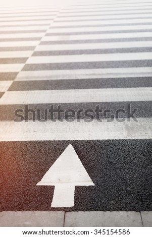 Zebra crossing and arrow signal on street at city - stock photo