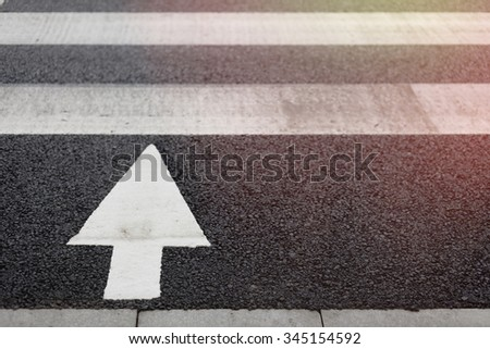 Zebra crossing and arrow signal on street at city