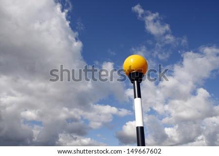 Zebra crossing belisha beacon light against a blue sky - stock photo