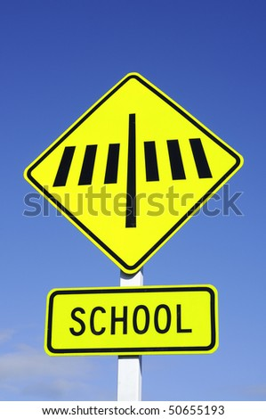 Zebra crossing sign with school set against blue sky - stock photo