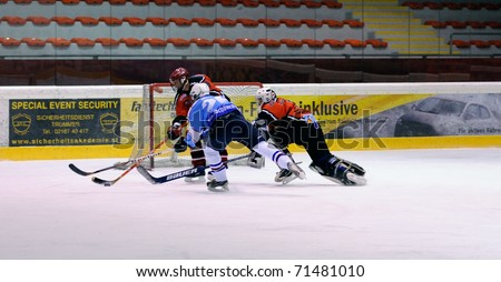 ZELL AM SEE, AUSTRIA - FEB 13: Salzburg hockey League. Goalie Hochwimmer dives to the net to save the puck. Game SV Schuttdorf vs HCS Morzg (9-3) on February 13, 2011 at the hockey rink Zell am See - stock photo