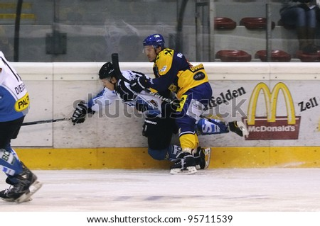 ZELL AM SEE; AUSTRIA - OCT 01: Austrian National League. A player of Linz (white jersey) gets hit by a player of EKZ. Game EK Zell am See vs Linz II (Result 5-2) on October 01, 2011 in Zell am See. - stock photo