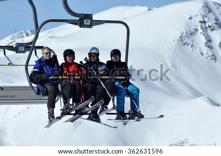 ZELL AM SEE - CCA. MARCH: Unidentified skiers going up with a ski lift and enjoying the last ski week of the season in March, 2012 in Zell am See, Austria - stock photo