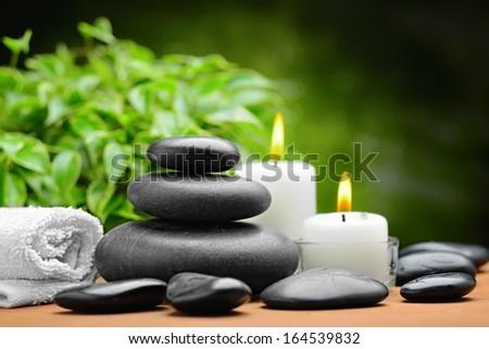 zen basalt stones and candle on the wood - stock photo