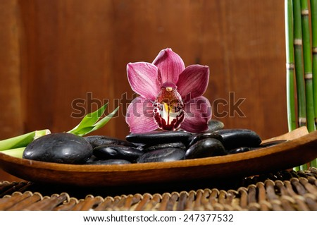 zen basalt stones with orchid on bowl, bamboo grove on mat - stock photo