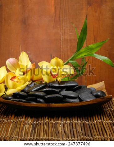 zen basalt stones with yellow orchid on bowl, bamboo on mat - stock photo