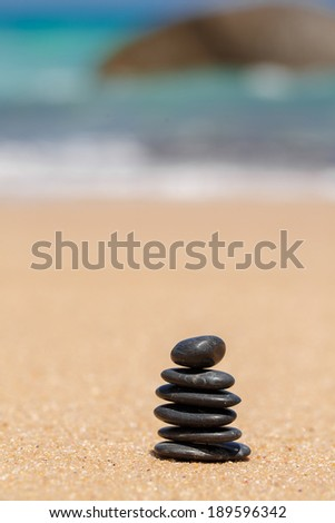 zen black stones laying on the beach near the water of ocean. Outdoors. Beach on the background