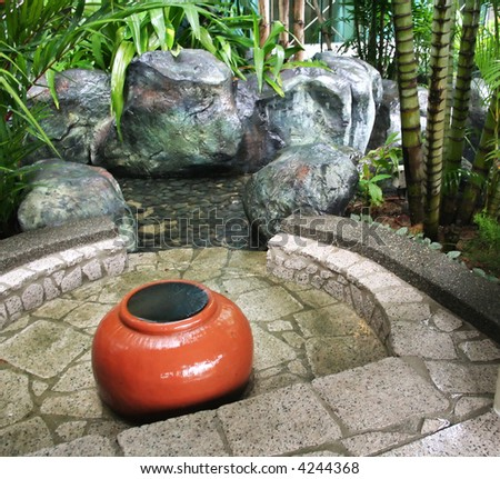 Zen garden fountain with ceramic pot and stones - stock photo