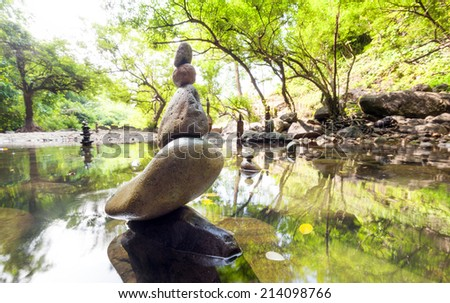 Zen garden. Meditate spiritual landscape of green forest with calm pond water and stone balance rocks - stock photo