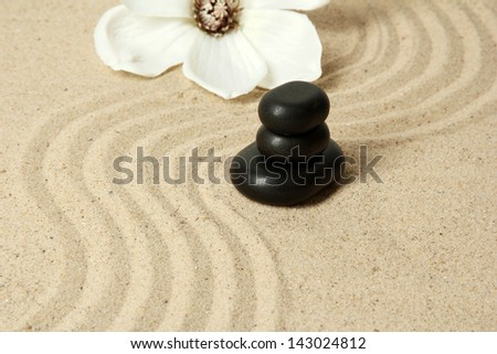 Zen garden with raked sand and round stones close up