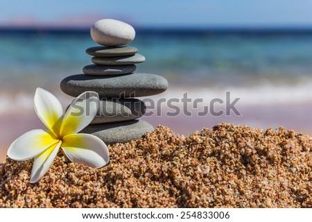 Zen meditation spa relaxation background - balanced stones stack with frangipani plumeria flower close up on sea beach - stock photo