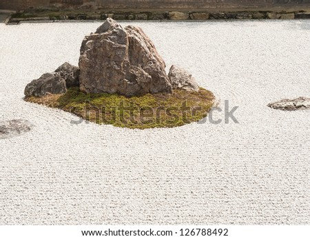 Zen Rock Garden in Ryoanji Temple.In a garden there are fifteen stones on white gravel. Kyoto.Japan. - stock photo