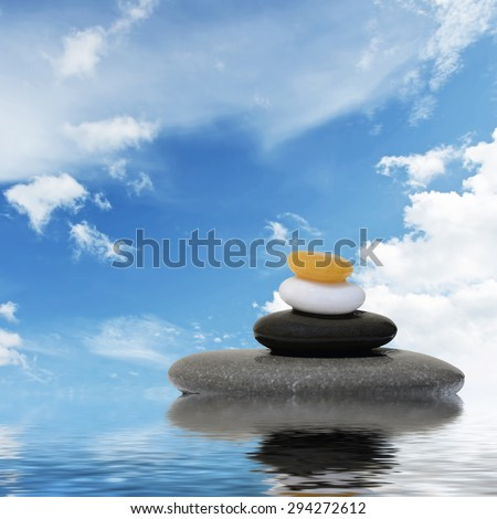 Zen spa concept background-Zen massage stones and orchid flowers reflected in water - stock photo