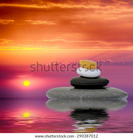 Zen spa concept background - Zen massage stones at sunset reflected in water - stock photo