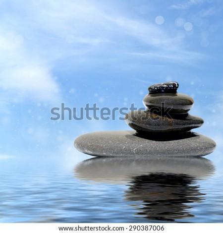Zen spa concept background - Zen massage stones reflected in water - stock photo