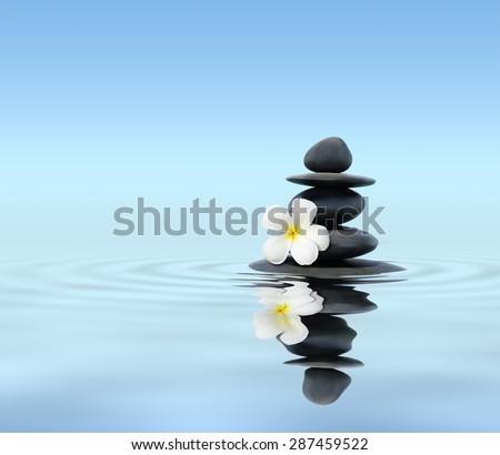 Zen spa concept background - Zen massage stones with frangipani plumeria flower in water reflection - stock photo