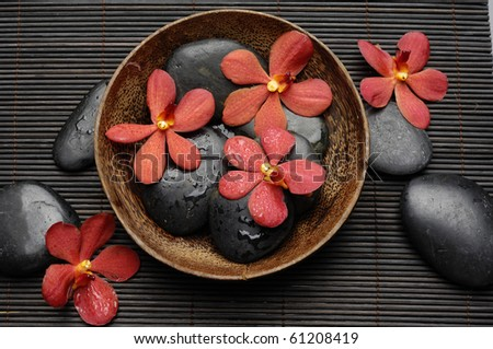 Zen Still Life-therapy stones with wooden bowl of set of red orchids on mat - stock photo