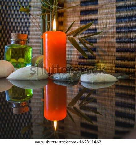 Zen stone and candles with reflections - stock photo