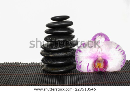 zen stones and orchid on bamboo mat - stock photo