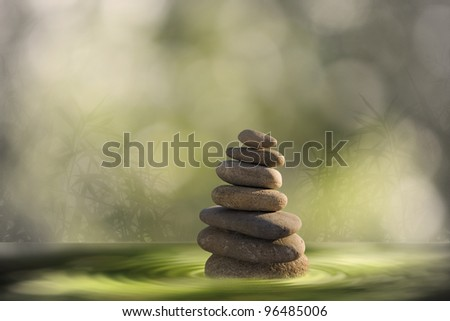 Zen stones tower in water with blurred background - stock photo