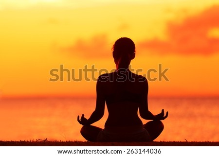Zen yoga woman doing meditation on beach - wellness concept. Female silhouette relaxing sitting at sunset background meditating at ocean retreat. Summer orange sunrise sky. - stock photo