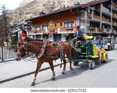 ZERMATT APR 14: Horse carriage for the hotel customer in Zermatt, Switzerland on April 14, 2011. Zermatt is famed as a mountaineering and ski resort of the Swiss Alps. - stock photo