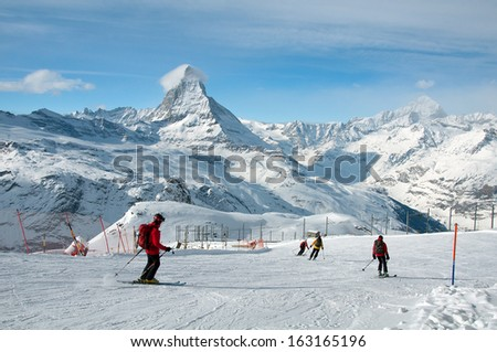 ZERMATT - JANUARY 17: Skiers Skiers downhill skiing from Gornergrat station on January 17, 2013 in Switzerland. The mountain village of Zermatt is one of the great ski center of the world. - stock photo