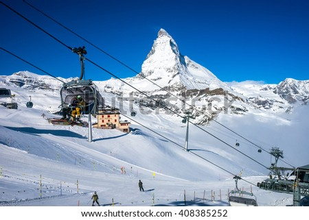 Zermatt, Switzerland- April 14,2016 : unidentified ski players in ski lift with Matterhorn Peak in background - stock photo