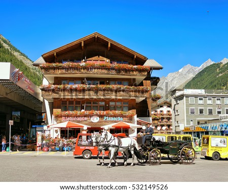 Zermatt, Switzerland - August 24, 2016: Horse vehicle and tourists at City center, Zermatt, Valais canton in Switzerland in summer.