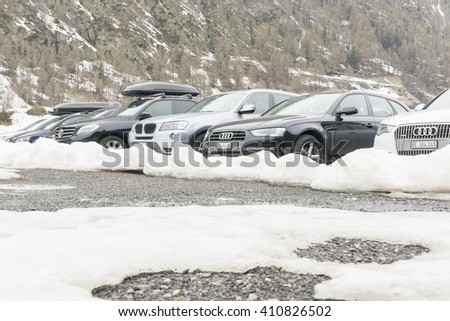 ZERMATT, SWITZERLAND - MARCH 29, 2016:  car parking at the street in Zermatt, Switzerland. Zermatt is a famous car-free ski resort in Switzerland.parking near the high Alpine mountain road and snow - stock photo