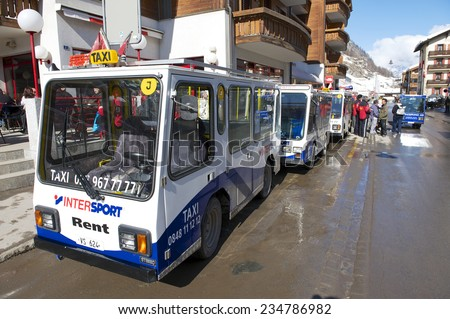 ZERMATT, SWITZERLAND - MARCH 03, 2009: Electro taxis wait for passengers in Zermatt, Switzerland. To prevent air pollution the entire town of Zermatt is a combustion-engine car-free zone. - stock photo