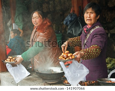 ZHANGJIAJIE - OCTOBER 27:  Chinese women sell roasted chestnuts to buyers in the market  on October, 27 2012 in Zhangjiajie, Hunan province, China. - stock photo