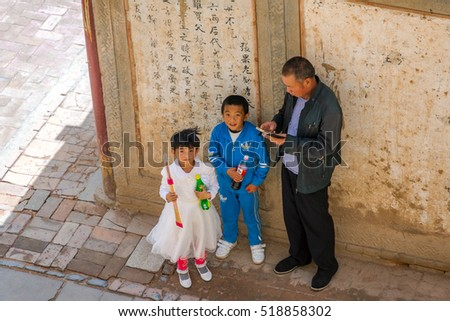 ZHANGYE, CHINA - JUNE 26: Boy and a girl with their father by the Hoof Temple, Mati Si cave temple, Gansu province. June 2016