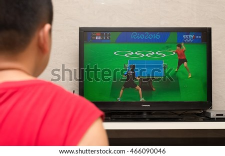 ZHONGSHAN GUANGDONG-August 9:a Chinese watching TV broadcasting pingpong match of the 2016 Summer Olympic Games in Rio de Janeiro, Brazil,the Olympic Games starts on August 5 till to August 21, 2016.