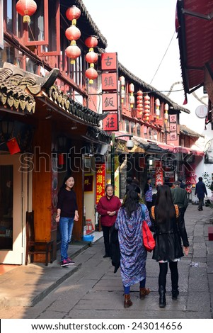 ZHUJIAJIAO, CHINA - NOVEMBER 10, 2014:  An unidentified saleswoman encourages people to come into her shop, one of many in the narrow streets of the ancient water town of Zhujiajiao, China - stock photo