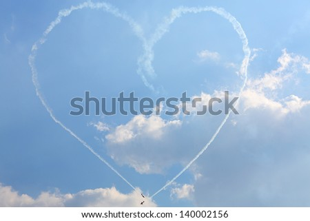 ZHUKOVSKY - AUGUST 12: Aircrafts paint big heart of smoke at airshow on 100th anniversary of Russian Air Force on August 12, 2012 in Zhukovsky, Moscow region, Russia. - stock photo