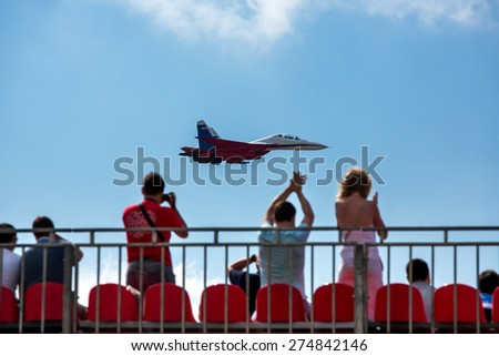 "ZHUKOVSKY, MOSCOW - AUG 16: Spectators in the stands and Russian fighter aircraft MIG-29 at ""AirShow Furious 2014"" on August 16, 2014 in Zhukovsky, Moscow region, Russia - stock photo"