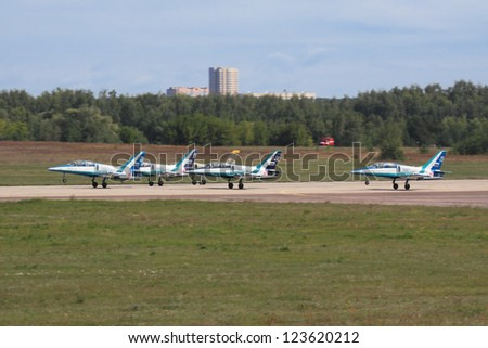 "ZHUKOVSKY, RUSSIA - AUGUST 19: Aerobatic team ""Rus"" on L39 planes on the runway the airfield Ramenskoe at the International Aviation and Space salon (MAKS) on August 19, 2011 in Zhukovsky, Russia - stock photo"
