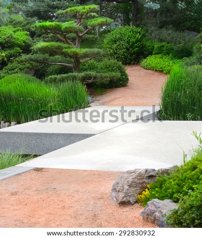 Zig-Zag bridge crossing over a stream leading to a Japanese Garden setting - stock photo