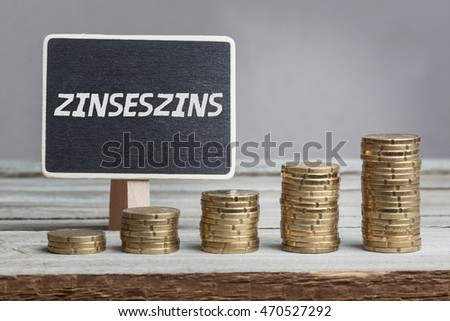 Zinseszins (compound interests)  in German language, white chalk type on black board, Euro money coin stacks of growth on wood table.